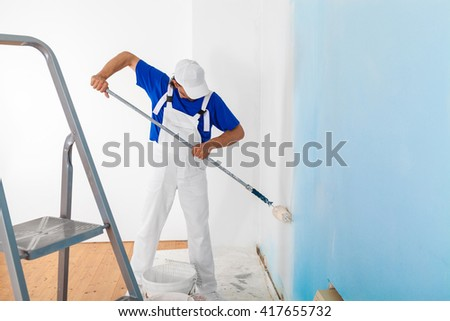 Side view of painter in white dungarees and cap painting a wall with paint roller; copy space