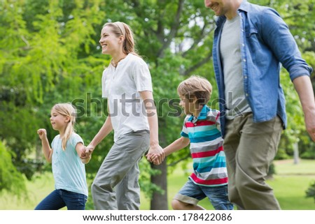 Side view of parents and kids walking in the park - stock photo