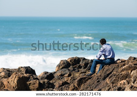 Side view of pensive, depressed man sitting on coast rock, looking at sea horizon.Copy space, unrecognizable person