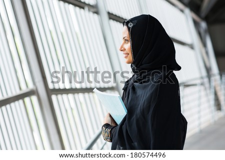 side view of pretty middle eastern college girl daydreaming - stock photo