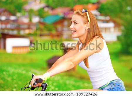 Side view of pretty woman enjoys biking in countryside in Alpine mountains, happy traveler resting outdoors, active summer vacation concept - stock photo