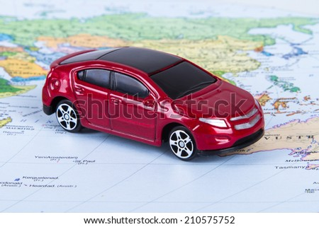 Side view of red, toy, small car on colorful map. - stock photo