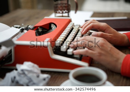 Side view of red typewriter, cup of coffe, crumpled paper - stock photo