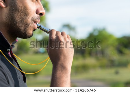 Side view of referee blowing whistle, selective focus