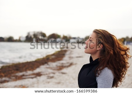 Side view of relaxed young female looking at sea. Beautiful caucasian woman looking at copyspace on beach. Female athlete resting after workout. - stock photo