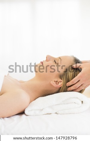 Side view of relaxed young woman receiving head massage at health spa