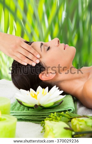 Side view of relaxed young woman receiving head massage at spa - stock photo