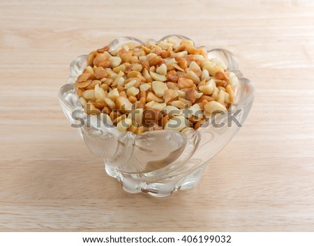 Side view of roasted and salted macadamia nut pieces in a glass bowl on a wood table top illuminated with natural light. - stock photo