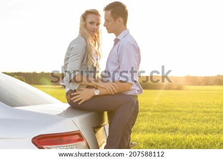 Side view of romantic young couple by car at countryside - stock photo