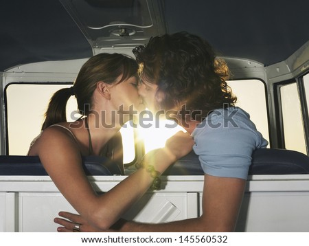 Side view of romantic young couple kissing in campervan - stock photo