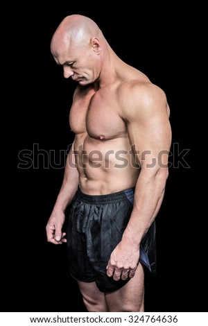 Side view of sad bald man looking down against black background - stock photo