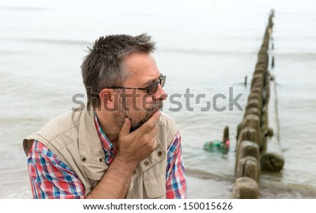 Side view of sad elderly man on the beach