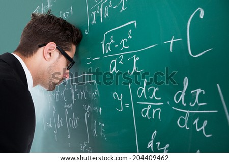 Side view of sad young male professor leaning head on blackboard in classroom - stock photo