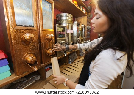 Side view of salesperson dispensing coffee beans into paper bag at store - stock photo