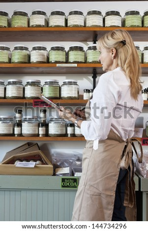 Side view of senior female employee going through list of spices in store - stock photo