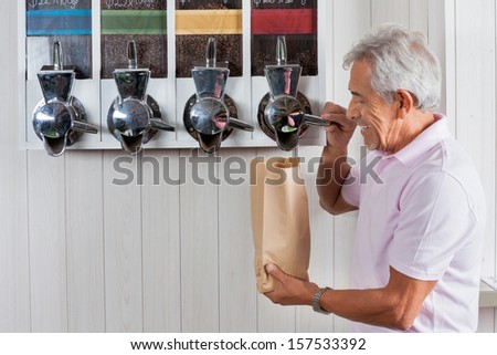 Side view of senior man buying coffee beans from vending machine at grocery store - stock photo