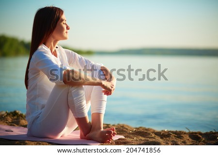 Side view of serene woman sitting on sandy beach against blue sky outdoors - stock photo