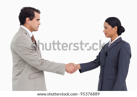 Side view of serious business partners shaking hands against a white background