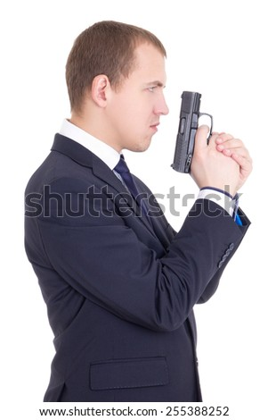 side view of serious man in business suit with gun isolated on white background - stock photo