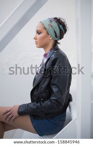 Side view of serious woman with hairband sitting on stairs - stock photo