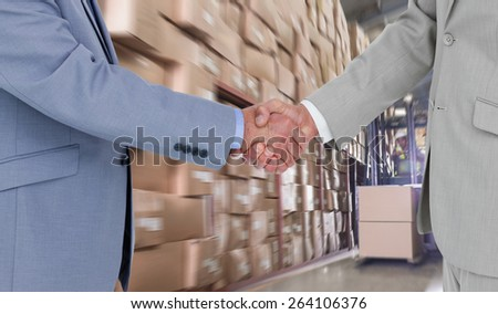 Side view of shaking hands against forklift machine in warehouse - stock photo