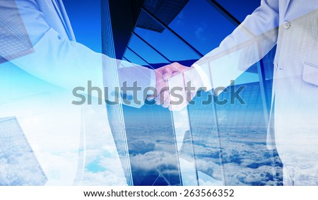 Side view of shaking hands against skyscraper - stock photo