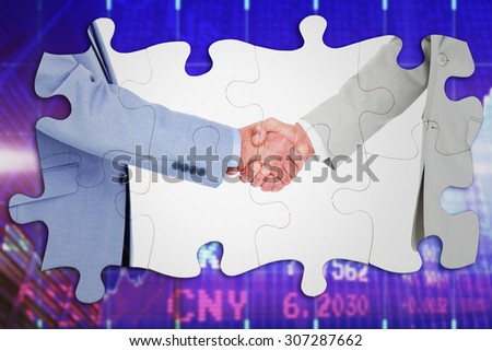 Side view of shaking hands against stocks and shares