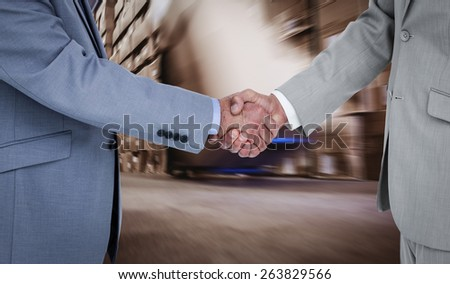 Side view of shaking hands against worker with fork pallet truck stacker in warehouse - stock photo