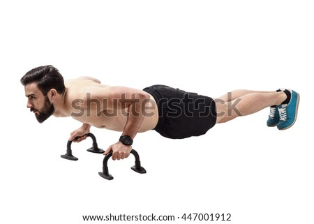Side view of shirtless fit athlete workout on push up handles. Full body length portrait isolated over white studio background. - stock photo