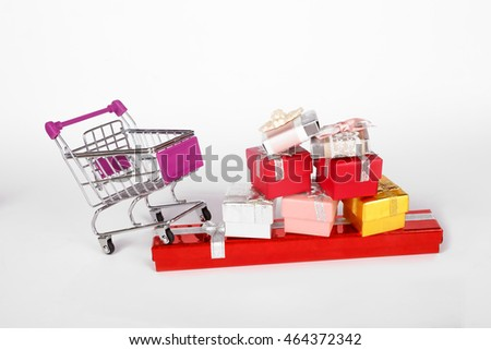 Side view of shopping card or trolley with colorful gift boxes isolated on white background.