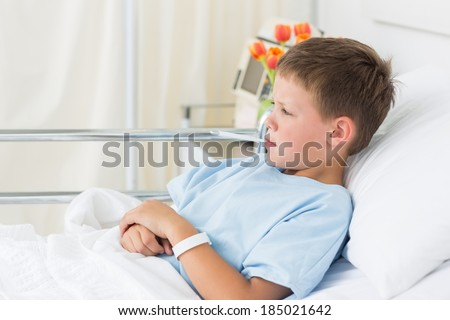 Side view of sick little boy in hospital with thermometer in mouth - stock photo