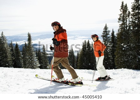 Side view of skiers on a snowy ski slope with trees and valley in background. Horizontal shot. - stock photo