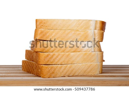 Side view of slices of toast bread on breadboard, isolated on white background.
