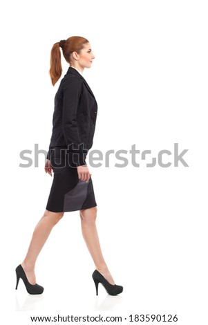 Side view of smiling and walking businesswoman in black suit, mini skirt and high heels. Full length studio shot isolated on white. - stock photo