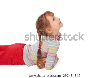 Side view of smiling child girl lying on stomach on the floor looking up at blank copy space, over white background  - stock photo