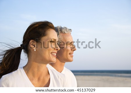Side view of smiling middle aged couple on beach looking off into the distance together. Horizontal shot. - stock photo