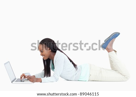 Side view of smiling woman on the floor with her laptop against a white background - stock photo