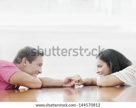 Side view of smiling young couple holding hands and looking at each other at table - stock photo