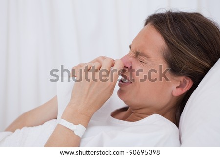 Side view of sneezing woman laying in bed - stock photo