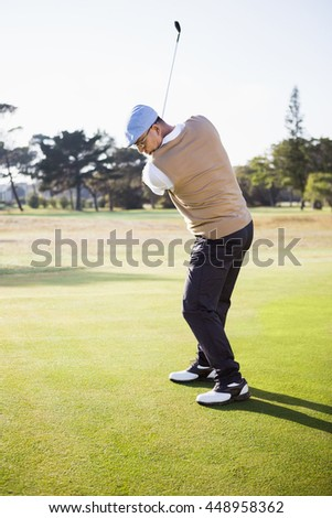 Side view of sportsman playing golf on a field - stock photo