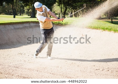 Side view of sportsman playing golf on a sandbox - stock photo