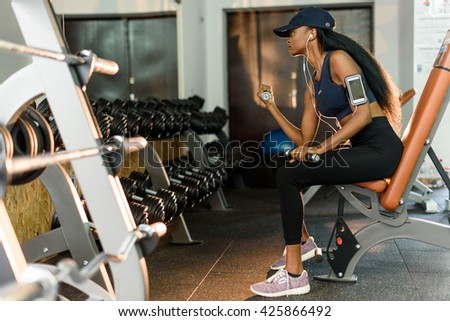 Side view of sporty fitness african american woman working out with dumbbells at the gym and listens music in earphones - stock photo