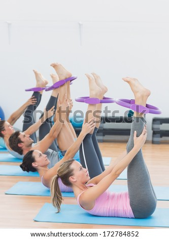Side view of sporty young people with exercising rings in fitness studio - stock photo