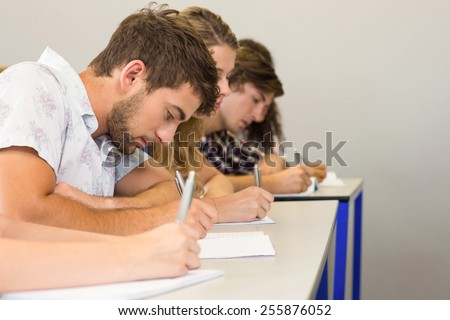 Side view of students writing notes in classroom
