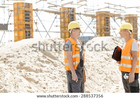 Side view of supervisors discussing at construction site - stock photo