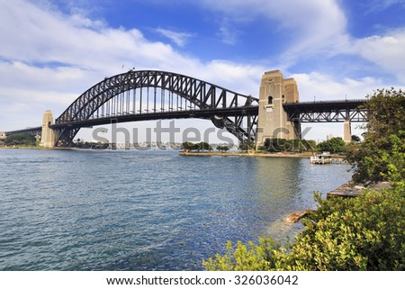 side-view of Sydney Harbour bridge from milsons point on bright summer sunny day with green trees surrounding harbour water - stock photo