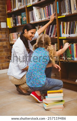 Side view of teacher and little girl selecting book in the library