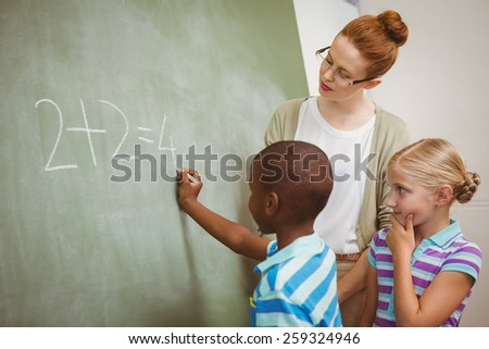 Side view of teacher assisting little boy to write on blackboard in the classroom - stock photo