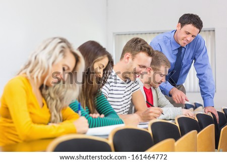 Side view of teacher with college students in row at the classroom - stock photo