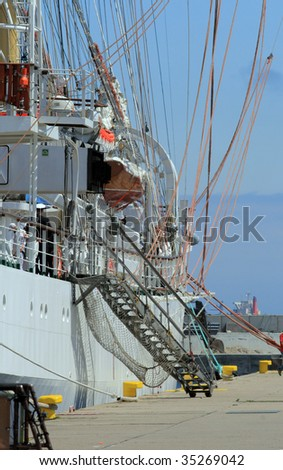 Side view of the historical yacht moored to the quay with ladder - stock photo